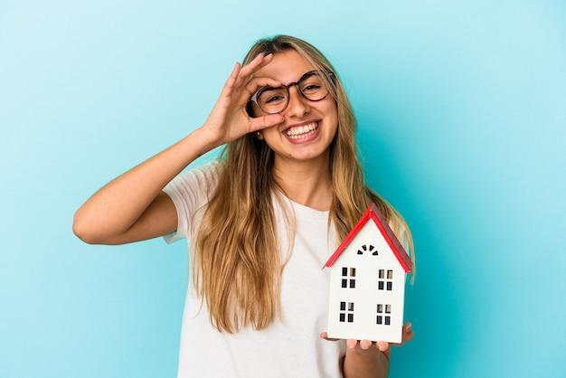 Jovem mulher caucasiana segurando um modelo de casa isolada na parede azul animada mantendo o gesto de ok no olho