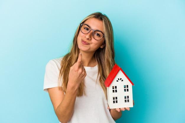 Jovem mulher caucasiana segurando um modelo de casa isolado em um fundo azul, apontando com o dedo para você como se fosse um convite para se aproximar.