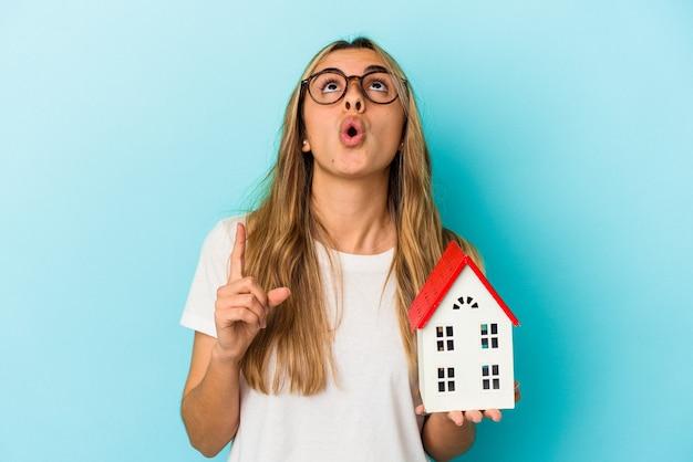 Jovem mulher caucasiana, segurando um modelo de casa isolado em um fundo azul, apontando para cima com a boca aberta.