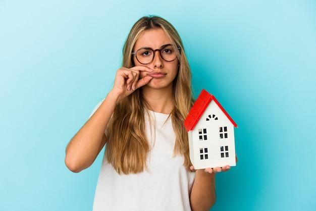 Jovem mulher caucasiana, segurando um modelo de casa isolado em um fundo azul com os dedos nos lábios, mantendo um segredo.