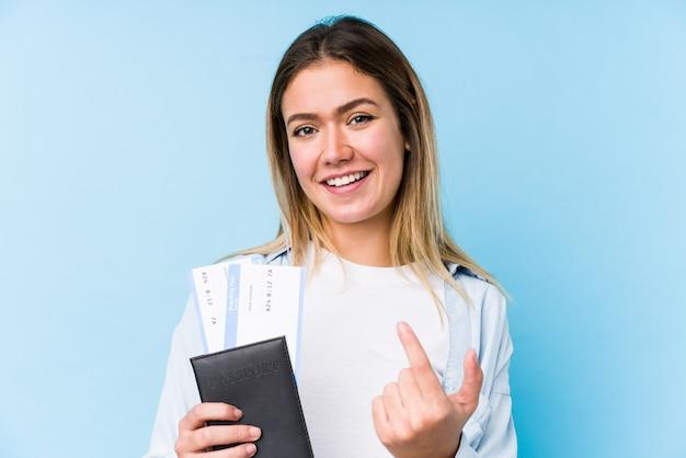 Jovem mulher caucasiana, segurando um passaporte isolado apontando com o dedo para você, como se convidando se aproximar.