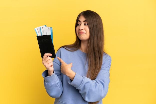 Jovem mulher caucasiana segurando um passaporte isolado em um fundo amarelo apontando para trás