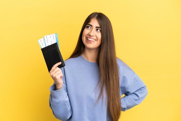Jovem mulher caucasiana segurando um passaporte isolado em um fundo amarelo, pensando em uma ideia enquanto olha para cima