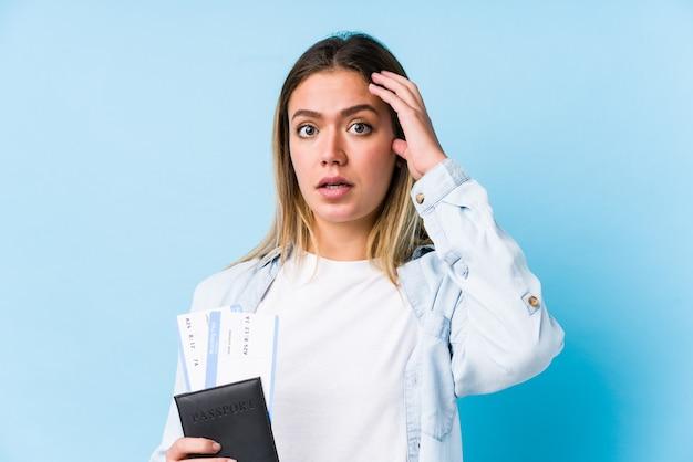 Jovem mulher caucasiana, segurando um passaporte isolado sendo chocada, ela se lembrou de uma reunião importante.