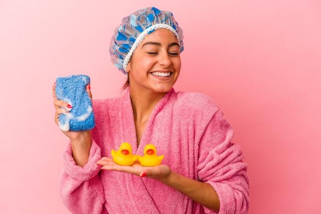 Jovem mulher caucasiana segurando um pato de plástico isolado em um fundo rosa