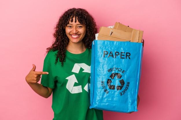 Jovem mulher caucasiana segurando um plástico reciclado isolado em um fundo rosa pessoa apontando com a mão para um espaço de cópia de camisa, orgulhosa e confiante