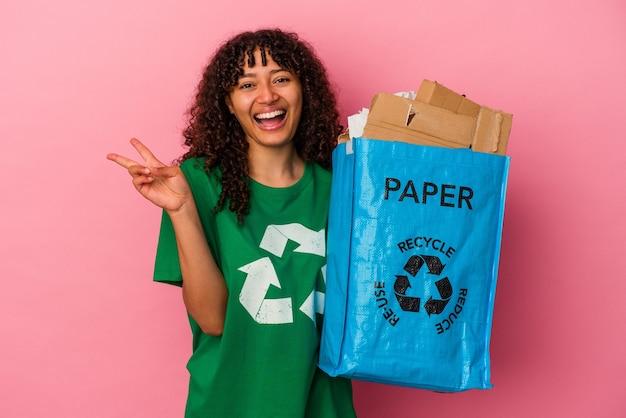 Jovem mulher caucasiana segurando um plástico reciclado isolado no fundo rosa, alegre e despreocupada, mostrando um símbolo de paz com os dedos.
