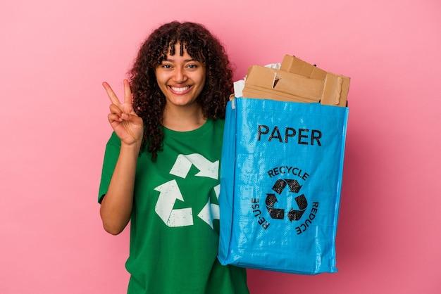 Jovem mulher caucasiana segurando um plástico reciclado isolado no fundo rosa, mostrando o número dois com os dedos.
