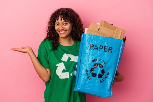 Jovem mulher caucasiana segurando um plástico reciclado isolado no fundo rosa, mostrando um espaço de cópia na palma da mão e segurando a outra mão na cintura.
