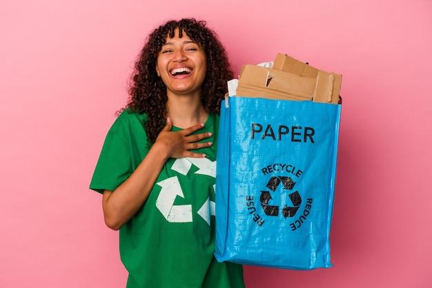 Jovem mulher caucasiana segurando um plástico reciclado isolado no fundo rosa ri alto, mantendo a mão no peito.
