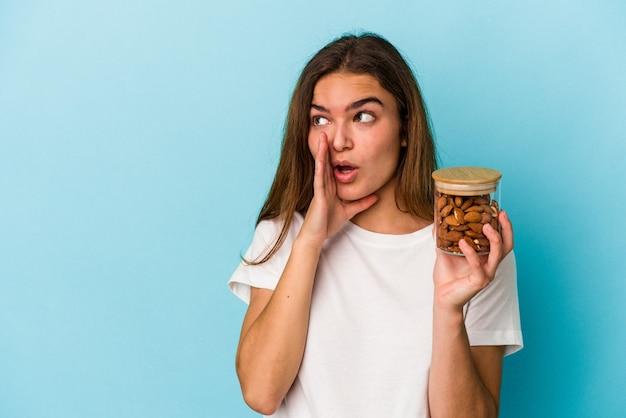 Jovem mulher caucasiana segurando um pote de amêndoa isolado em um fundo azul está contando uma notícia secreta de travagem e olhando para o lado