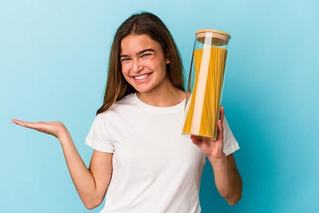 Jovem mulher caucasiana segurando um pote de macarrão isolado em um fundo azul, mostrando um espaço de cópia na palma da mão e segurando a outra mão na cintura.