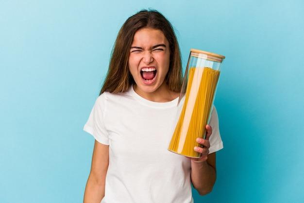 Jovem mulher caucasiana segurando um pote de macarrão isolado no fundo azul, gritando com muita raiva e agressividade.