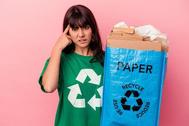 Jovem mulher caucasiana segurando um saco de papelão reciclado isolado no fundo rosa, mostrando um gesto de decepção com o dedo indicador.