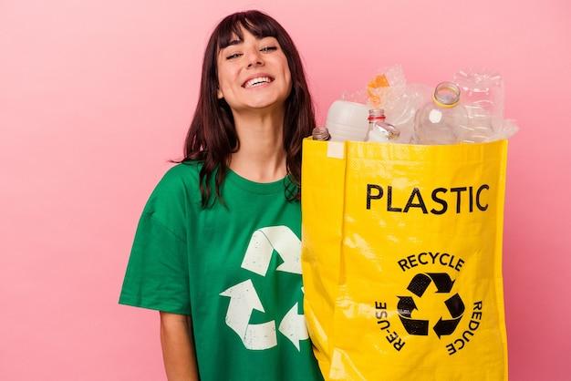 Jovem mulher caucasiana segurando um saco plástico reciclado, isolado na parede rosa, rindo e se divertindo.