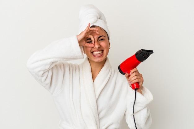 Jovem mulher caucasiana, segurando um secador de cabelo isolado no branco, animado, mantendo o gesto de ok no olho.