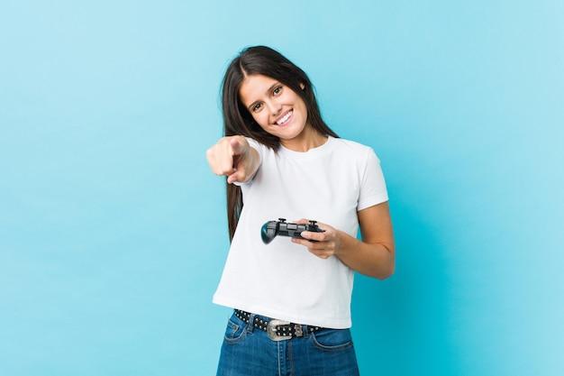 Jovem mulher caucasiana, segurando um sorriso alegre de controlador de jogo, apontando para a frente.