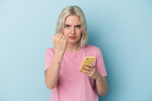 Jovem mulher caucasiana, segurando um telefone celular isolado em um fundo azul, mostrando o punho para a câmera, expressão facial agressiva.