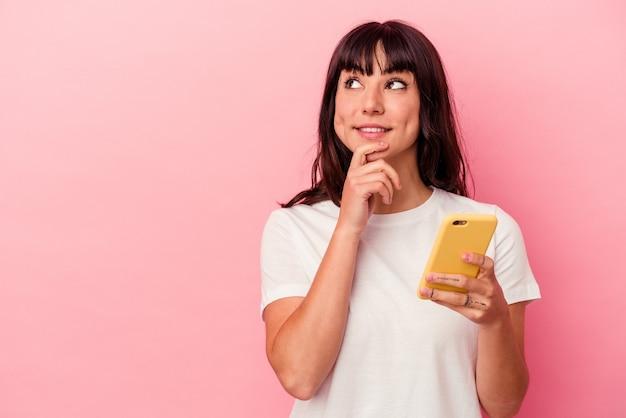 Jovem mulher caucasiana, segurando um telefone celular isolado no fundo rosa, olhando de soslaio com expressão duvidosa e cética.
