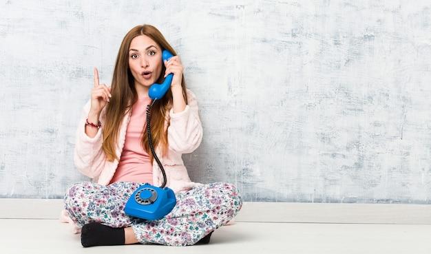 Jovem mulher caucasiana, segurando um telefone fixo, tendo uma ótima ideia, o conceito de criatividade.