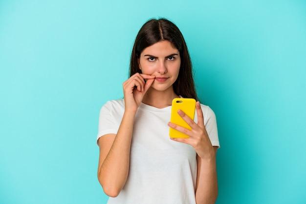 Jovem mulher caucasiana, segurando um telefone móvel isolado em um fundo azul com os dedos nos lábios, mantendo um segredo.