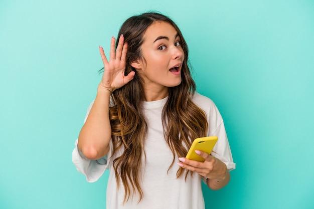 Jovem mulher caucasiana, segurando um telefone móvel isolado em um fundo azul, tentando ouvir uma fofoca.