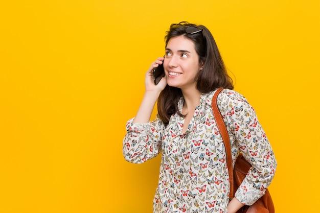 Jovem mulher caucasiana, segurando um telefone