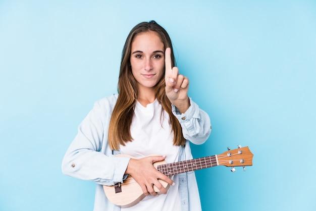 Jovem mulher caucasiana, segurando um ukelele mostrando o número um com o dedo.