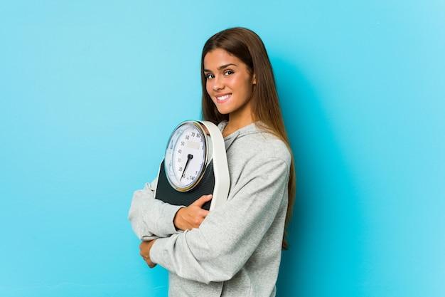 Jovem mulher caucasiana, segurando uma balança isolada em uma parede azul