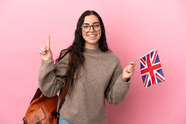 Jovem mulher caucasiana segurando uma bandeira do reino unido isolada em um fundo rosa apontando uma ótima ideia