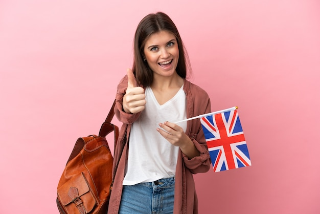 Jovem mulher caucasiana segurando uma bandeira do reino unido isolada em um fundo rosa com o polegar para cima porque algo de bom aconteceu