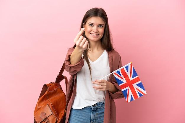 Jovem mulher caucasiana segurando uma bandeira do reino unido isolada em um fundo rosa fazendo gesto de dinheiro