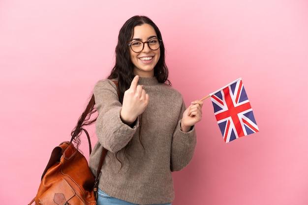 Jovem mulher caucasiana segurando uma bandeira do reino unido isolada em um fundo rosa fazendo um gesto de aproximação