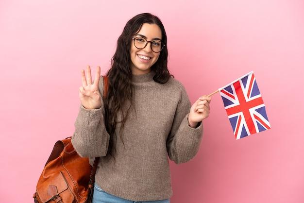 Jovem mulher caucasiana segurando uma bandeira do reino unido isolada em um fundo rosa feliz e contando três com os dedos