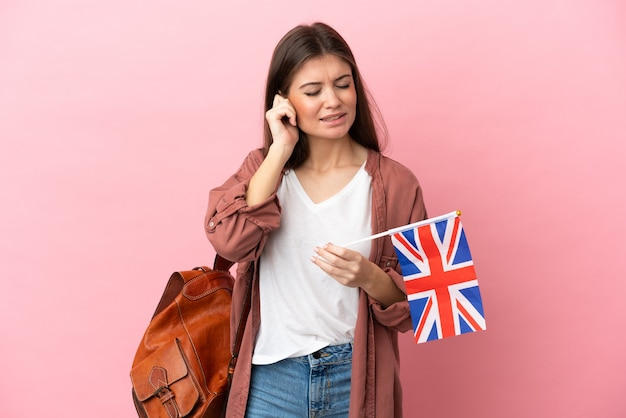 Jovem mulher caucasiana segurando uma bandeira do reino unido isolada em um fundo rosa frustrada e cobrindo as orelhas