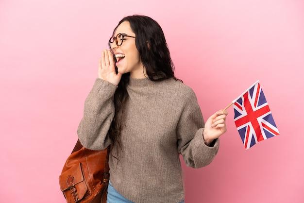 Jovem mulher caucasiana segurando uma bandeira do reino unido isolada em um fundo rosa gritando com a boca bem aberta para o lado