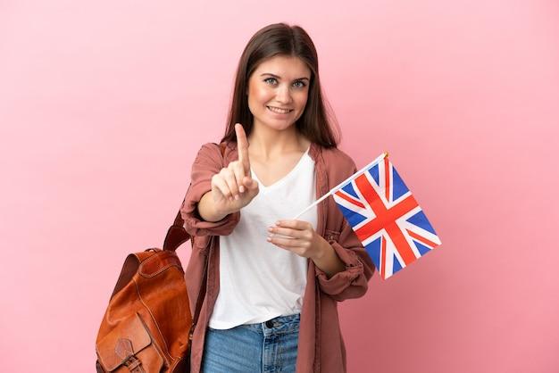 Jovem mulher caucasiana segurando uma bandeira do reino unido isolada em um fundo rosa, mostrando e levantando um dedo