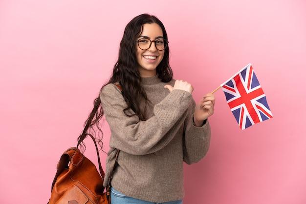 Jovem mulher caucasiana segurando uma bandeira do reino unido isolada em um fundo rosa, orgulhosa e satisfeita