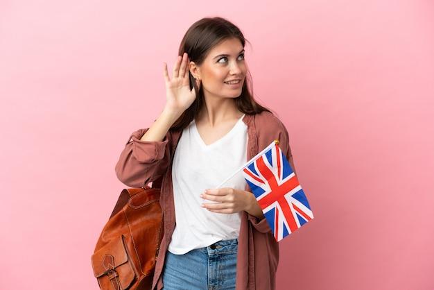 Jovem mulher caucasiana segurando uma bandeira do reino unido isolada em um fundo rosa, ouvindo algo colocando a mão na orelha