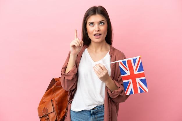 Jovem mulher caucasiana segurando uma bandeira do reino unido isolada em um fundo rosa, pensando em uma ideia apontando o dedo para cima