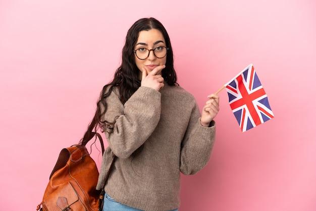 Jovem mulher caucasiana segurando uma bandeira do reino unido isolada em um fundo rosa pensando