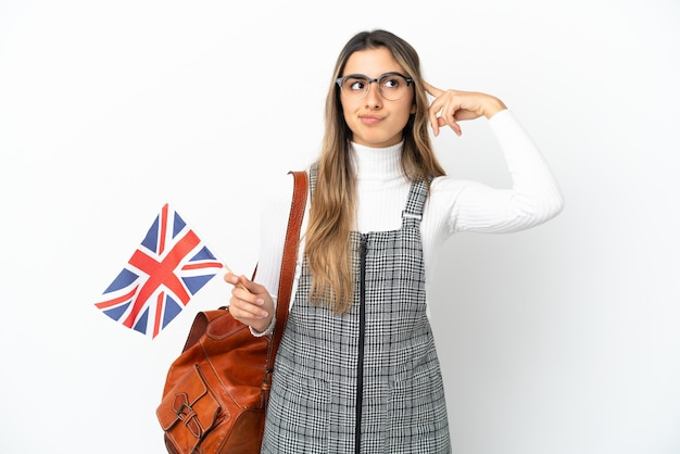 Jovem mulher caucasiana segurando uma bandeira do reino unido, isolada no fundo branco, tendo dúvidas e pensando