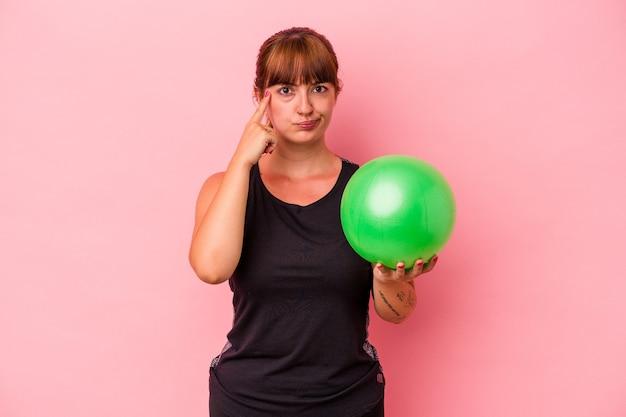 Jovem mulher caucasiana, segurando uma bola para fazer esporte isolado no fundo rosa, apontando o templo com o dedo, pensando, focado em uma tarefa.