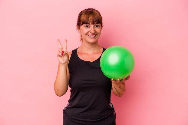 Jovem mulher caucasiana, segurando uma bola para fazer esporte isolado no fundo rosa, mostrando o número dois com os dedos.