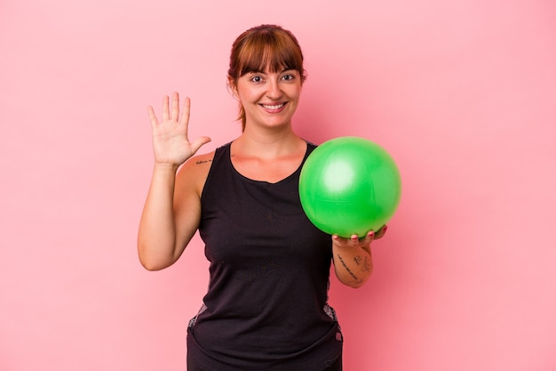 Jovem mulher caucasiana, segurando uma bola para fazer esporte isolado no fundo rosa, sorrindo alegre mostrando o número cinco com os dedos.