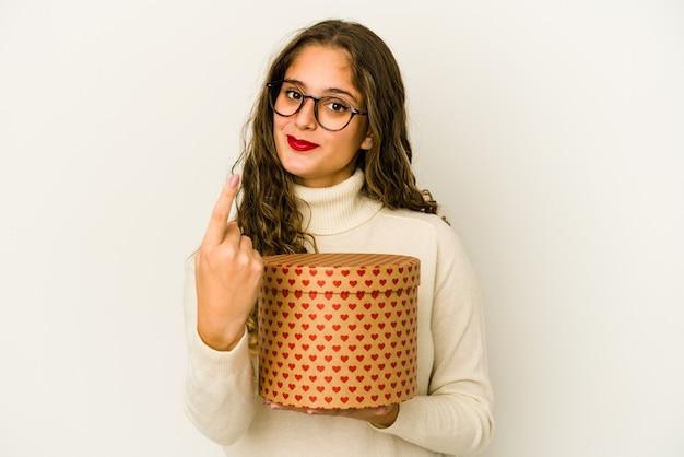 Jovem mulher caucasiana segurando uma caixa de dia dos namorados coração isolada apontando com o dedo para você como se estivesse convidando a se aproximar.