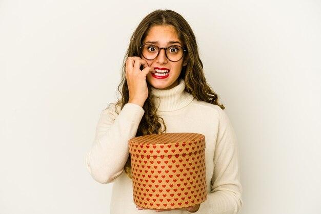 Jovem mulher caucasiana, segurando uma caixa de dia dos namorados coração isolada unhas roendo, nervosa e muito ansiosa.