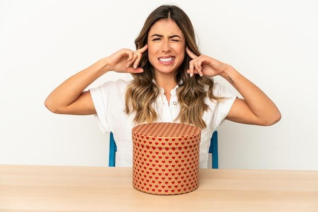 Jovem mulher caucasiana segurando uma caixa de dia dos namorados isolada, cobrindo as orelhas com as mãos.