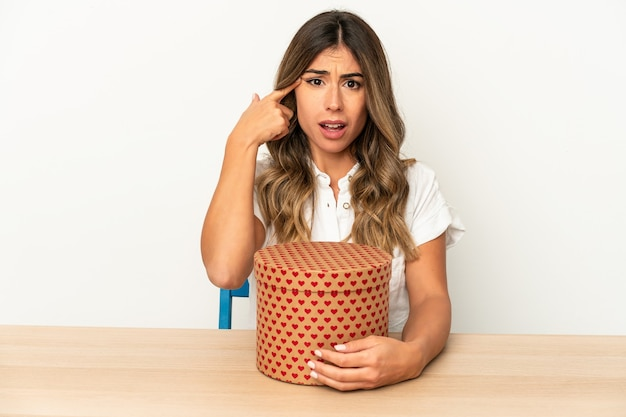 Jovem mulher caucasiana segurando uma caixa de dia dos namorados isolada, mostrando um gesto de decepção com o dedo indicador.
