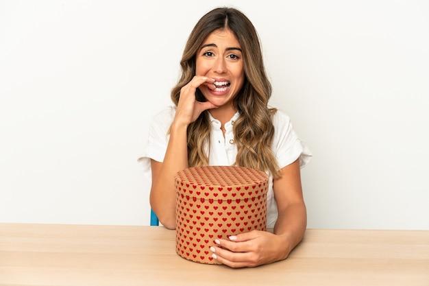 Jovem mulher caucasiana, segurando uma caixa de dia dos namorados isolada unhas roendo, nervosa e muito ansiosa.